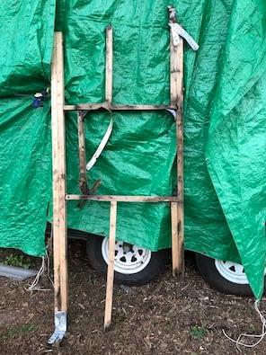 old rotten wooden frame against green tarp