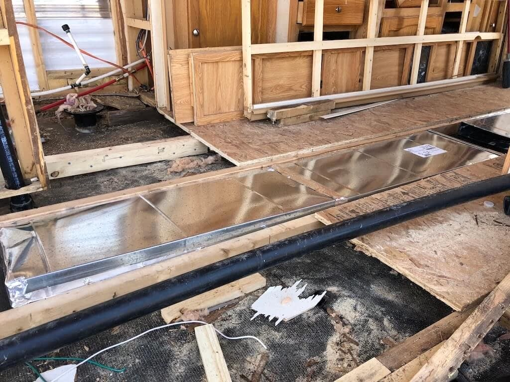 shiny air duct in between wooden trailer floor supports