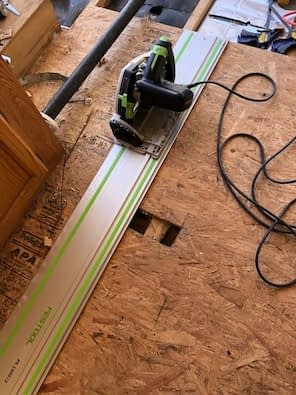 a track saw on a track on old particle board trailer floor
