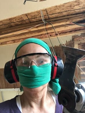 Woman with green fabric covering head and nose and mouth, safety glasses and red ear protectors