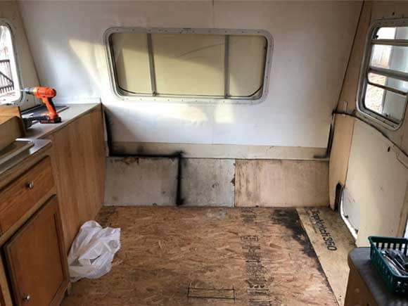 Dinette area of camper after furniture, floor tile and lower walls were removed. There is significant rot showing on floor and walls.