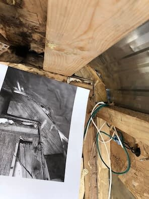 black and white photo held up next to old wooden framing