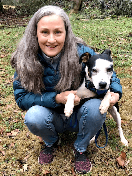 Picture of Camper Woman, Kirsten, a middle-aged woman with long salt-and-pepper hair, with her small black and white dog, Poppy